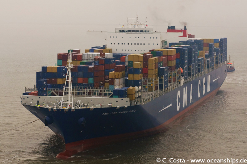 The huge vessel slowly comes out of the fog entering the port of Bremerhaven.